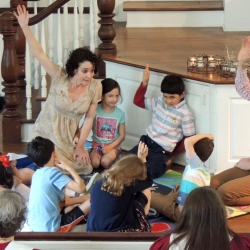 Children and adults sit on the floor and listen to the children's sermon