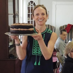 A woman carries a cake