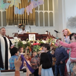 Children wave decorative butterflies while singing Alleluia