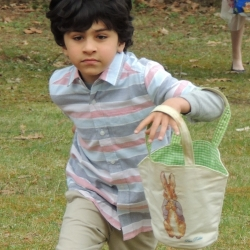 A boy runs across the lawn looking for Easter eggs