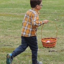 A boy runs across the lawn in search of Easter eggs