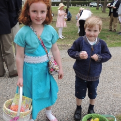 A brother and sister hold their Easter eggs up proudly
