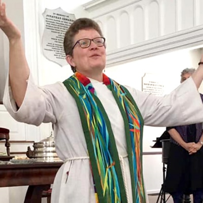 Rev. Patty Fox lifts her hands before the congregation in a blessing