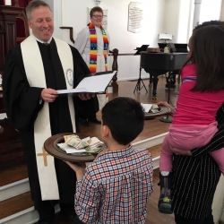 Rev. Brent Damrow receives the offering from a group of children