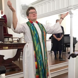 Rev. Patty Fox lifts her hands before the congregation in blessing