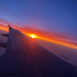 The wing of a plane as the sun rises
