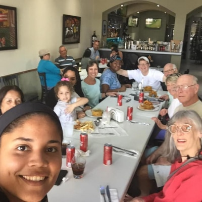 Volunteers pose at a meal table for a selfie