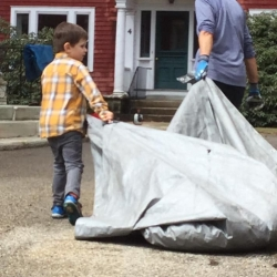 A young boy helps haul a tarp with leaves