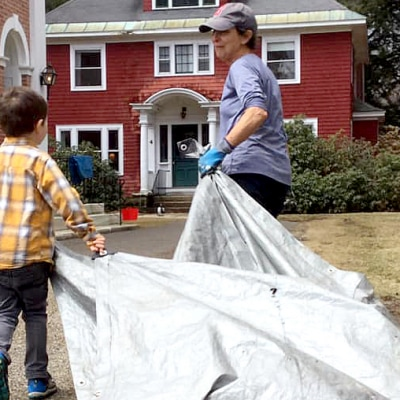 A boy helps haul leaves in a tarp
