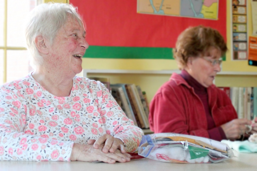 A woman crochets while another woman smiles