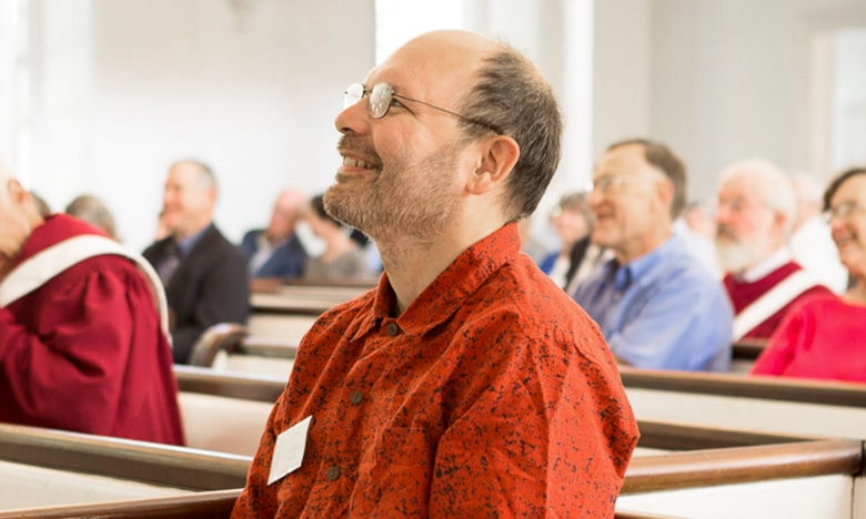 A man smiles while listening to a sermon
