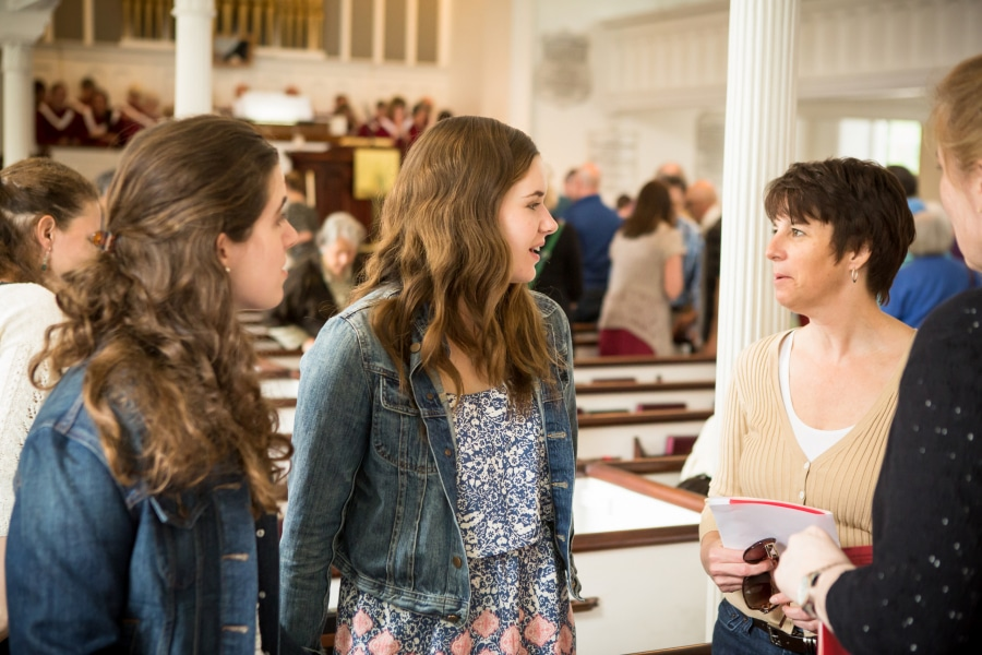 A woman chats with two young women in the sanctuary
