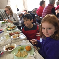 Two children eat at a potluck