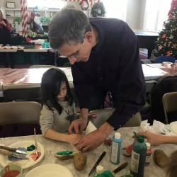 An older man demonstrates to a young girl how to stamp paint with a homemade potato stamp