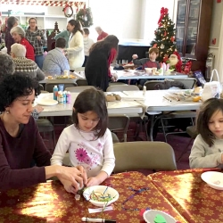 Two girls and a mother make Christmas ornaments