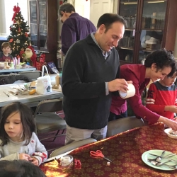 Two parents and their children make Christmas ornaments