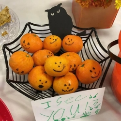 A baskety of clementines decorated for Halloween