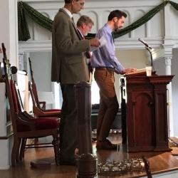 A young man reads from the pulpit
