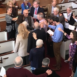 Congregants lay their hands on Pastor Brent to bless him
