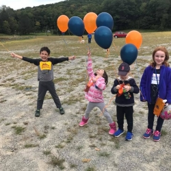 A group of kids holding balloons