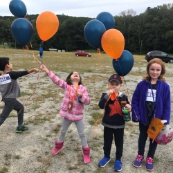 A group of kids holding a balloon
