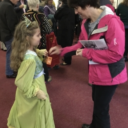 A girl dressed as a princess receives a donation