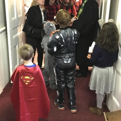 Children in Halloween costumes await adults coming out of worship