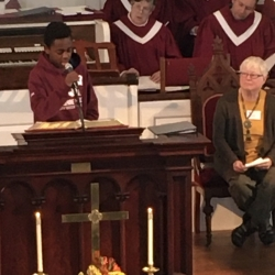 A teenage boy reads scripture in the pulpit