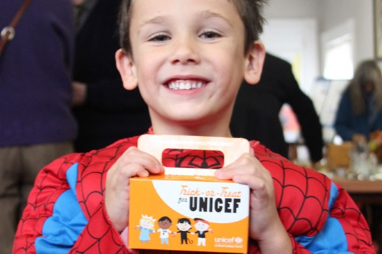 A boy dressed as Spiderman trick-or-treats for UNICEF