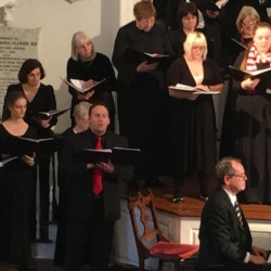 Tenor soloist Steve Hassmer sings a solo while accompanied by chorus and piano