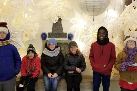 A group of pre-teens in front of a winter lights display