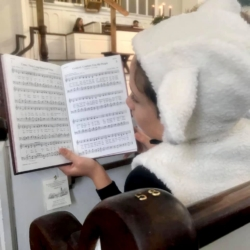 A boy dressed as a sheep sings from a hymnal