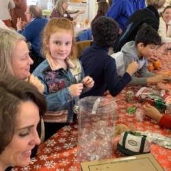 Children and parents work on Christmas ornaments