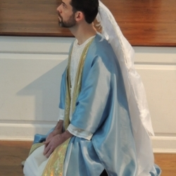 A man dressed as the Archangel Gabriel kneels before the voice of God