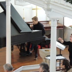 A young man plays the piano while the choir director conducts