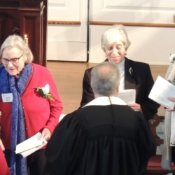 The pastor shakes the hand of an older woman to welcome her into the church