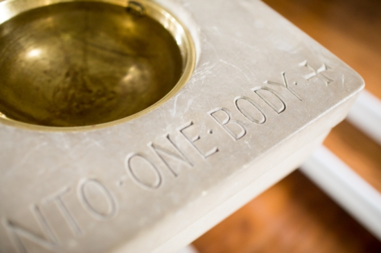 """Baptismal fond with the words """"one body"""" engraved"""