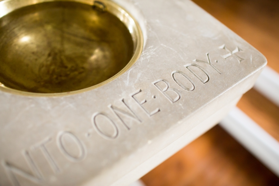 "Baptismal fond with the words ""one body"" engraved"