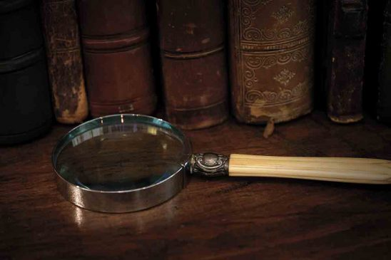 Free stock photo Close-up of magnifying glass by hardcover books on wooden table