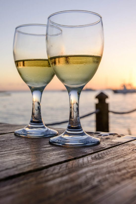 Free stock photo Close-up of white wineglasses on table at beach during sunset