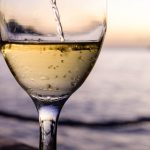 Free stock photo Close-up of white wine being poured in wineglass at beach