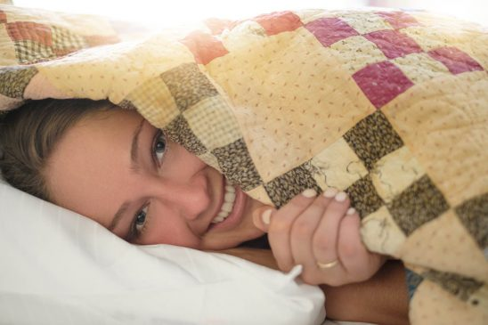 Free stock photo Close-up portrait of young woman smiling while covering self with duvet in bed