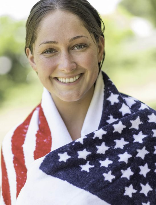 Free stock photo Portrait of confident young woman wrapped in american flag