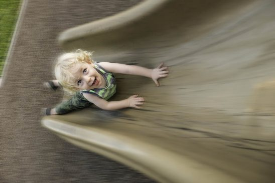 Free stock photo High angle view of boy playing on slide in playground