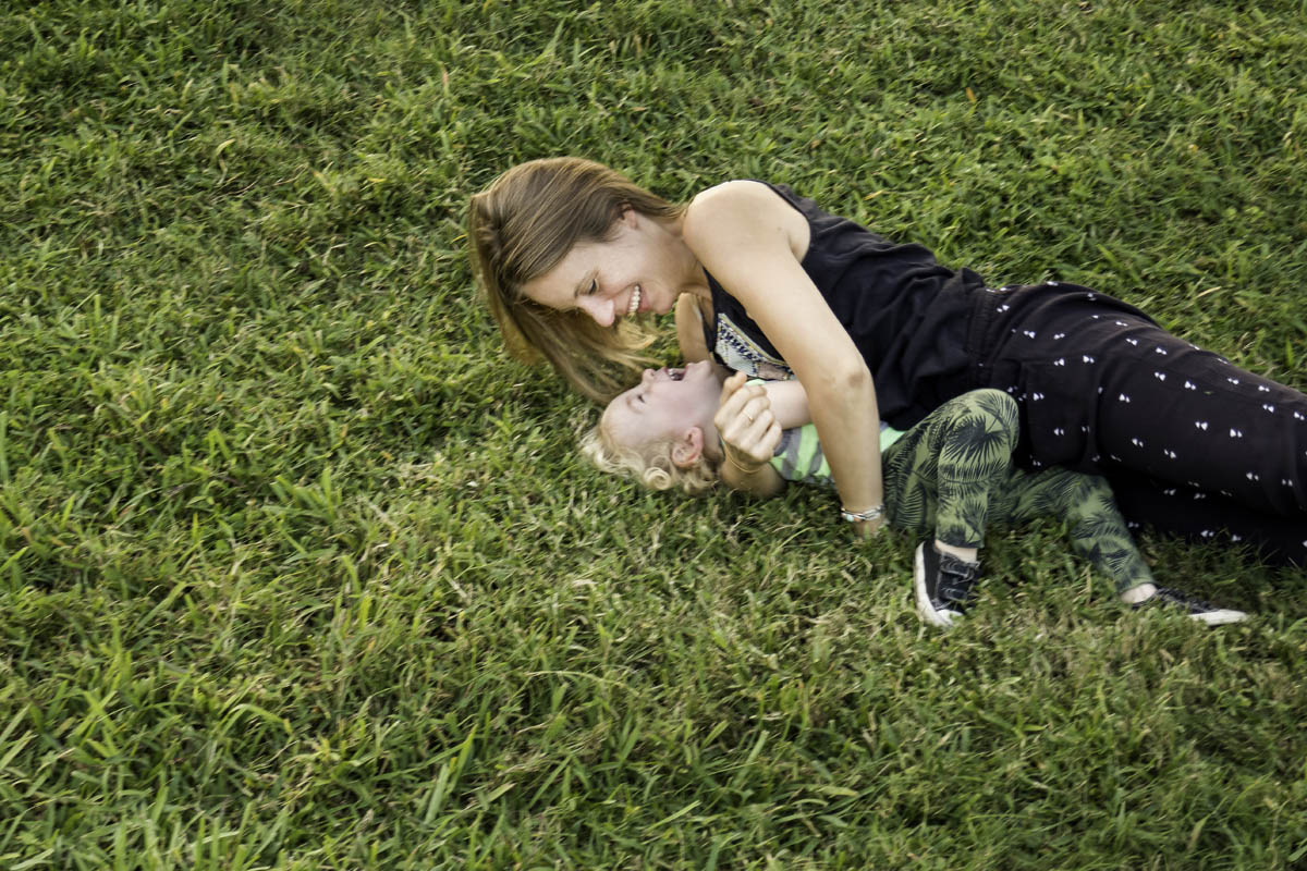 Free stock photo Playful mother and son lying on grassy field