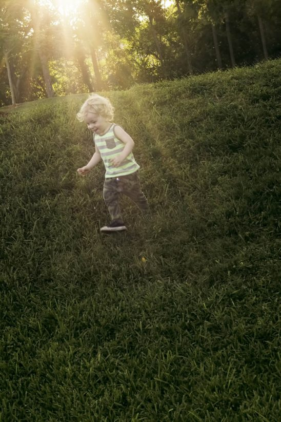 Free stock photo Boy running on grassy field on sunny day