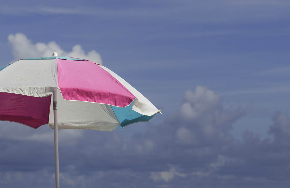 Free stock photo Sunshade at beach against cloudy sky