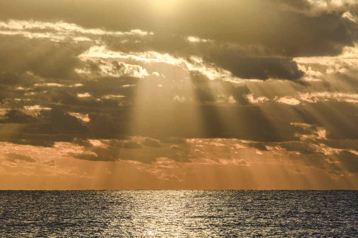 Free stock photo Sunbeams shining through clouds over sea during sunset