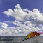 Free stock photo Colorful sunshade by sea against cloudy sky