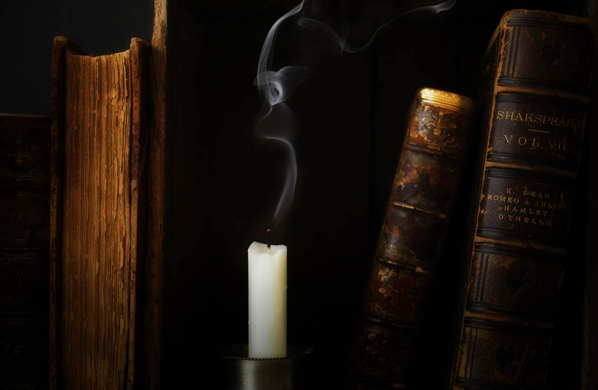 Free stock photo Extinguished candle amidst hardcover books on table